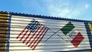 US and MX flags painted on the border fence.