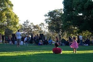 Little girl and others enjoying the music in the park