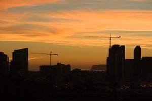 Sunset and cranes over downtown