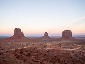 Monument Valley sunset, start of moon rise between the mittens